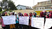 """Para buruh yang sebagian besar perempuan membawa spanduk bertuliskan """"Tolak RUU Omnibus Law""""."""