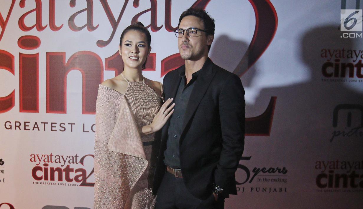 Penyanyi Raisa dan suaminya, Hamish Daud berpose saat menghadiri gala premiere film Ayat Ayat Cinta 2 di Jakarta, Kamis (07/12). (Liputan6.com/Herman Zakharia)