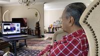 Foto memperlihatkan mantan Perdana Menteri (PM) Malaysia, Mahatir Mohamad, mengikuti parlemen digital yang membuat warganet salah fokus pada dekorasi rumahnya. (dok. Twitter @chedetofficial)