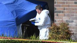 Seorang tim investigasi mengecek barang bukti di lokasi penembakan massal di Borderline Bar & Grill di Thousand di Thousand Oaks, California (8/11). Pelaku penembakan tewas dengan melakukan tembakan bunuh diri. (AFP Photo/Robyn Beck)