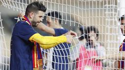 Bek Barcelona, Gerard Pique, melakukan selebrasi dengan menggunting jaring gawang usai menjuarai Copa del Rey di Stadion Olimpico de Sevilla, Minggu (18/4/2021). Barcelona menang 4-0 atas Athletic Bilbao. (AP Photo/Angel Fernandez)