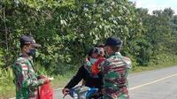 TNI Kodim 1206/Putussibau, Kapuas Hulu punya cara agar warga patuh protokol kesehatan (prokes) Covid-19 di perbatasan Malaysia, salah satunya yakni dengan pembagian masker gratis. (Foto: Liputan6.com/Aceng Muakaram)