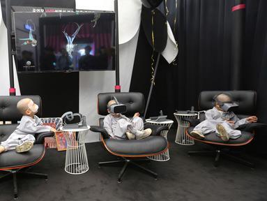 Empat anak lelaki berkepala botak bermain Virtual Reality (VR) menggunakan layanan 5G di tempat pengalaman LG UPlus 5G di Seoul, Korea Selatan (7/5/ 2019). Sepuluh anak terpilih mendapatkan pengalaman menjadi biksu dalam rangkaian acara peringatan hari lahir Buddha. (AP Photo/Ahn Young-joon)