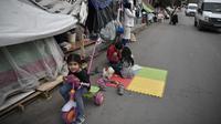 Anak-anak bermain di sebuah jalan di luar kamp pengungsi Eleonas di Athena (20/11/2019). Yunani akan menutup tiga kamp migran terbesarnya di pulau-pulau yang menghadap Turki, dan menggantinya dengan fasilitas baru yang lebih ketat untuk identifikasi, relokasi dan deportasi. (AFP/Louisa Gouliamaki)