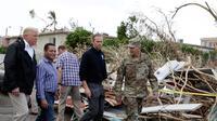Presiden AS Donald Trump berkeliling ke permukiman warga yang rusak akibat terjangan Badai Maria di Guaynabo, Puerto Rico, Selasa (3/10). Trump menyaksikan langsung kehancuran akibat badai di Puerto Rico dan bertemu para pemimpin pulau itu (AP/Evan Vucci)