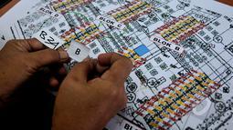 """Pedagang Kaki Lima Monas diundi untuk mendapatkan posisi kios dalam program Pemerintah Daerah dalam penataan PKL lewat program """"Lenggang Jakarta"""", Kamis (9/4/2015). Tampak petugas sedang mencocokkan nomor dengan posisi kios. (Liputan6.com/Johan Tallo)"""