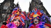 Perempuan dengan kostum warna-warni berpose di depan katedral Cologne saat puluhan ribu orang menyambut dimulainya musim karnaval di jalan-jalan Kota Cologne, Jerman, Senin (11/11/2019). Musim karnaval ini dikenal juga sebagai musim kelima dalam satu tahun. (AP Photo/Martin Meissner)