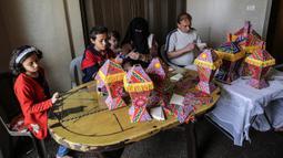 Anggota keluarga Palestina al-Yaqoubi berkumpul di sekitar meja membuat lentera bulan suci Ramadan untuk dijual selama penerapan lockdown di Khan Yunis, di Jalur Gaza selatan pada 15 April 2020. Karena pandemi Covid-19, keadaan berubah dan tradisi Ramadan pun tidak akan ada. (SAID KHATIB / AFP)