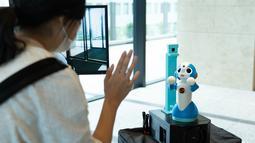 Seorang pengunjung berinteraksi dengan robot dalam uji coba yang dilakukan di sebuah bangunan komersial di Tokyo, Jepang (14/9/2020). Ajang ini untuk menguji coba cara kerja robot dalam memandu, memeriksa suhu, telepresensi, dan sejumlah fungsi lainnya. (Xinhua/Pemerintah Kota Metropolitan Tokyo)