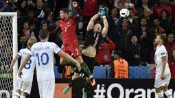 Kiper Islandia, Hannes Halldersson, menepis sundulan bintang Portugal, Cristiano Ronaldo, pada laga Grup F Piala Eropa di Stadion Geoffroy Guichard, St Etienne, Rabu (14/6/2016). Islandia bermain imbang 1-1 dengan Portugal. (AFP/Jeff Pachoud)