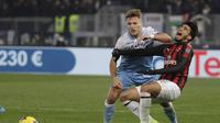 Penyerang SS LAzio, Ciro Immobile hentikan pergerakan Lucas Paqueta pada laga semifinal Coppa Italia yang berlangsung di stadion Olimpico, Roma, Rabu (27/2). AC Milan bermain imbang 0-0 kontra SS Lazio. (AP Newsroom)