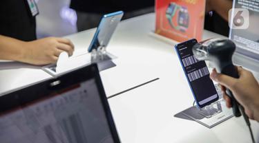 Petugas toko memindai IMEI handphone untuk didata di ITC Roxy Mas, Jakarta, Selasa (26/11/2019). Pemerintah melalui Kemendag, Kemenperin, dan Kemenkominfo menerbitkan regulasi pemblokiran ponsel ilegal melalui nomor IMEI yang disahkan pada 18 Oktober 2019. (Liputan6.com/Faizal Fanani)