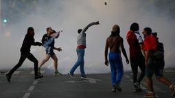 Seorang pria melemparkan batu ke arah petugas saat melakukan protes di bawah Menara Eiffel di dekat zona penggemar Paris sebelum laga Portugal vs Prancis di Final EURO 2016 di Prancis (10/6). (REUTERS/Stephane Mahe)