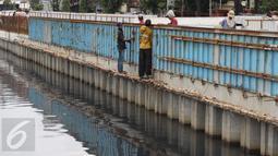 Para pekerja menyelesaikan pembangunan turap di sepanjang Kali Grogol, Jakarta, Senin (21/11). Pembangunan turap dilakukan untuk mencegah meluapnya air kali saat hujan dan ditargetkan selesai 20 Desember 2016. (Liputan6.com/Gempur M Surya)