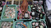 Penjual menunjukkan gantungan kunci berlogo Muktamar ke-33 Nahdlatul Ulama di Jombang, Jawa Timur, Senin (3/8/2015). Pernak-pernik yang dijual yakni kaos, pin, gantungan kunci, dan berbagai produk kerajinan tangan lainnya. (Liputan6.com/Johan Tallo)
