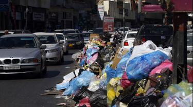 Kendaraan melintas di samping tumpukan sampah di sepanjang sisi jalan di Tripoli, ibukota Libya (30/9/2019). Berton-ton sampah berserakan dari tempat sampah dan menumpuk di pinggir jalan. (AFP Photo/Mahmud Turkia)