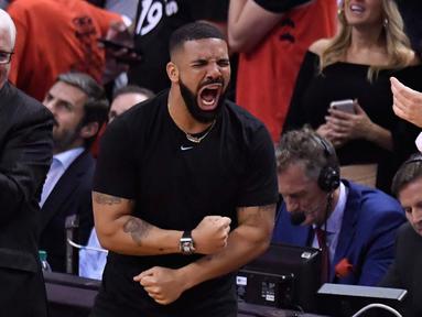 Penyanyi Rapper Drake bersorak saat menyaksikan pertandingan kelima Final NBA 2019 antara Golden State Warriors melawan Toronto Raptors di Scotiabank Arena, Toronto, Ontario (11/6/2019). Warriors mengalahkan Toronto Raptors dengan 106-105. (Frank Gunn/The Canadian Press via AP)