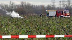 Pemadam kebakaran memeriksa lokasi terjadinya kecelakaan udara antara pesawat kecil dengan helikopter di Philippsburg, Jerman, Selasa (23/1).  Helikopter yang terlibat dalam kecelakaan ini diketahui merupakan ambulans udara.  (Rene Priebe/dpa via AP)