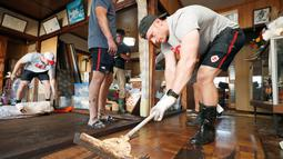 Pemain rugby Kanada Peter Nelson secara sukarela membersihkan lumpur dari sebuah rumah di Kamaishi, Prefektur Iwate, Jepang, Minggu (13/10/2019). Topan Hagibis membuat pertandingan Rugby World Cup Pool B antara Kanada dengan Namibia dibatalkan. (Kyodo News via AP)
