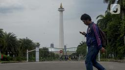Pejalan kaki berjalan di kawasan Monumen Nasional (Monas) yang akan dijadikan arena lintasan balapan Formula E 2020, Jakarta, Selasa (11/2/2020). Ajang ini dilakukan di kawasan Monas setelah mendapatkan persetujuan dari Komisi Pengarah Kawasan Medan Merdeka. (merdeka.com/Imam Buhori)