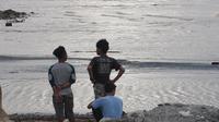 Sejumlah remaja sedang menyaksikan kemunculan buaya muara Sungai Palu untuk menunggu waktu berbuka puasa, Rabu (20/5/2020). (Foto: Heri Susanto/ Liputan6.com).