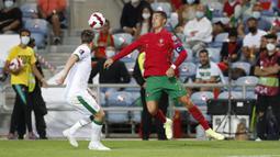 Pemain Portugal Cristiano Ronaldo (kanan) mengontrol bola saat melawan Irlandia pada pertandingan kualifikasi grup A Piala Dunia 2022 di Stadion Algarve, luar Faro, Portugal, Rabu (1/9/2021). Ronaldo mencetak dua gol saat Portugal menang 2-1. (AP Photo/Armando Franca)