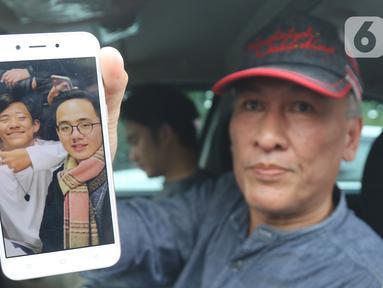 Pihak keluarga menunjukan foto anggota saat menunggu kepulangan WNI yang sudah selesai menjalani observasi di Natuna, di Bandara Halim Perdana Kusuma, Jakarta, Sabtu (15/2/2020). Pemerintah resmi memulangkan 238 WNI ke daerah masing-masing karena telah dinyatakan sehat (Liputan6.com/Herman Zakharia)