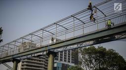 Pekerja menyelesaikan pembangunan bagian atap halte busway BNN di Kawasan Cawang Jakarta, Jumat (2/3). Pembangunan halte baru tersebut guna menggantikan halte BNN yang lama akibat pembangunan proyek LRT. (Liputan6.com/Faizal Fanani)