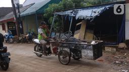 Pengumpul barang bekas berkeliling di Ciledug Indah, Tangerang, Banten, Senin (21/2./2021). Pasca banjir melanda perumahan tersebut menjadi berkah bagi para pengumpul barang rongsok karena banyak barang yang di buang pemilik rumah. (Liputan6.com/Angga Yuniar)