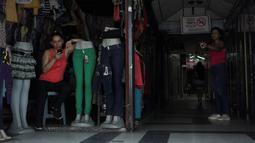Seorang wanita bermain ponsel di sebuah toko selama pemadaman listrik di San Cristobal, Venezuela (26/3). Ponsel yang selalu aktif digunakan untuk berkomunikasi maupun sebagai penerangan darurat sulit untuk bertahan tanpa adanya listrik. (Reuters/Carlos Eduardo Ramirez)