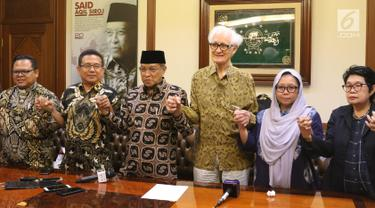 Ketua Umum PBNU, KH Said Aqil Siradj bersama Pdt Gomar Gultom (PGI), Romo Heri Wibowo (KWI), Romo Franz Magnis Suseno, Anyir Sulaiman (UKI) dan Alissa Wahid (GNI) bergandengan tangan usai menyerukan perdamaian di Papua, di Jakarta, Senin (9/9/2019). (Liputan6.com/Angga Yuniar)