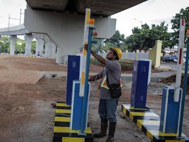 Pekerja mengecek pintu parkir di lahan yang dijadikan park and ride untuk stasiun MRT (Moda Raya Terpadu) Lebak Bulus, Jakarta, Selasa (20/3). Dua stasiun MRT dilengkapi dengan park and ride untuk fasilitas penumpang. (Liputan6.com/Faizal Fanani)