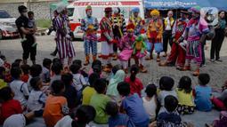 Anak-anak menyaksikan aksi badut yang tergabung dalam komunitas Aku Badut Indonesia (ABI) di pengungsian korban banjir di Gor Pangadegan, Jakarta, Selasa (7/1/2020). Trauma healing diberikan para badut sebagai bentuk kepedulian terhadap anak-anak korban banjir Jakarta. (Liputan6.com/Faizal Fanani)