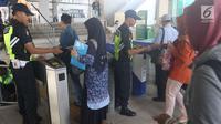 Petugas stasiun mengecek tiket penumpang di Stasiun Depok Baru, Jawa Barat, Senin (23/7). PT Kereta Commuter Indonesia (KCI) di wilayah Jabodetabek memberlakukan pembelian tiket kertas pengganti tiket elektronik KRL. (Liputan6.com/Immanuel Antonius)