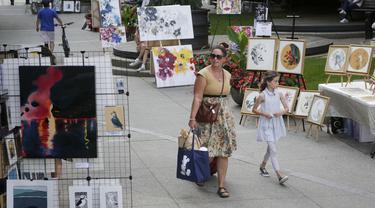 Sejumlah orang mengamati karya seni yang dipajang di area terbuka dalam pameran Art Downtown, Vancouver, British Columbia, Kanada, 4 September 2020. Art Downtown merupakan proyek yang memungkinkan seniman dan publik saling terhubung dan menginspirasi serta berbagi kreativitas. (Xinhua/Liang Sen)