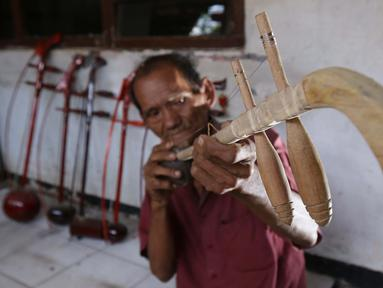 Ghohyong mengecek alat musik Tehyan buatannya di Neglasari, Kota Tangerang (5/2/2021). Ghohyong merupakan pria tua yang ahli membuat dan mahir memainkan alat musik Tehyan khas Tionghoa. (Liputan6.com/Angga Yuniar)