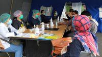 Petugas kesehatan di Posko Tanggap Darurat Corona Covid-19 Kota Malang bersiap memeriksa kesehatan para santri yang baru pulang dari pondok pesantren (Liputan6.com/Zainul Arifin)