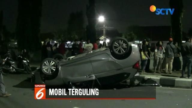 Diduga pengemudi bertengkar dengan tunangannya, sebuah mobil sedan terguling di Jalan Cempaka Putih Barat, Jakarta, Minggu (25/11) malam.