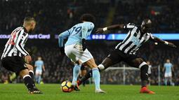 Gelandang Manchester City, Leroy Sane berebut bola dengan pemain Newcastle United, DeAndre Yedlin dan Mohamed Diame pada pertandingan pekan ke-24 Premier League di Etihad Stadium, Minggu (21/1). Manchester City meraih kemenangan 3-1. (Oli SCARFF/AFP)