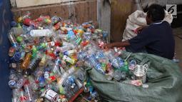 Pemulung membersihkan botol-botol plastik yang diambil dari tumpukan sampah di Pintu Air Manggarai, Jakarta, Jumat (26/4). Selanjutnya, botol-botol plastik bekas minuman kemasan ini akan dijual ke pengepul. (Liputan6.com/Helmi Fithriansyah)