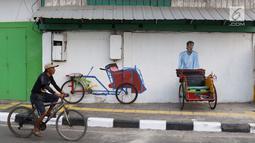 Pengendara sepeda melintas di depan Kampung Tematik Sketsa di kawasan Penjaringan, Jakarta Utara, Rabu (1/7). Sketsa-sketsa yang menghiasi kawasan tersebut dibuat dalam rangka menyambut Asian Games XVIII Tahun 2018. (Liputan6.com/Immanuel Antonius)