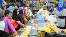 Pedagang kue kering melayani pembeli di Pasar Jatinegara, Jakarta, Senin (27/5/2019). Jelang Idul Fitri 2019, banyak warga berburu makanan ringan seperti kue kering untuk jamuan di hari raya. (Liputan6.com/Angga Yuniar)