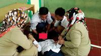 Guru dan siswa berusaha menenangkan siswi yang kesurupan. (Foto: Liputan6.com/Muhamad Ridlo)