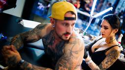 Seniman wanita mentato badan pengunjung dalam acara edisi keempat Montreux Tattoo Convention di Montreux, Swiss  (22/9). Lebih 150 seniman tato dari 22 negara berkumpul dalam acara tersebut. (Valentin Flauraud/Keystone via AP)
