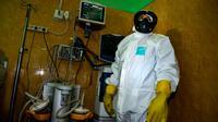 Petugas medis dengan pakaian pelindung menyiapkan ruang isolasi di sebuah rumah sakit di Banda Aceh, Selasa (3/3/2020). Di Aceh, dua rumah sakit menjadi rujukan pasien virus Corona, yakni Rumah Sakit Umum dr Zainoel Abidin (RSUZA) Banda Aceh dan RSUD Cut Meutia, Aceh Utara. (CHAIDEER MAHYUDDIN/AFP)