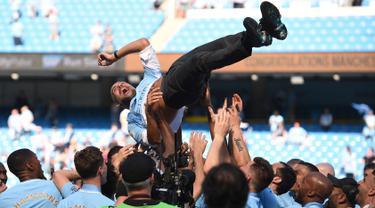 Manajer Manchester City Pep Guardiola dilemparkan ke udara oleh para pemainnya usai melawan Huddesfiel dalam pertandingan Liga Inggris di Etihad Stadium (6/5). (AFP/Oli Scraff)