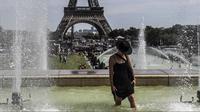 Seorang wanita mendinginkan kakinya di sebuah kolam di Trocadero Fountains dekat Menara Eiffel, Paris (22/7/2019). Warga Paris bersiap menghadapi suhu terpanas pada minggu ini ketika gelombang panas akan melanda ke Eropa utara. (AFP Photo/Alain Jocard)