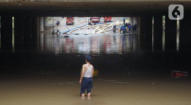Petugas berdiri di antara banjir yang menggenangi underpass Kemayoran, Jakarta, Senin (3/2/2020). Curah hujan tinggi menyebabkan banjir yang menggenangi kawasan tersebut lama surut sehingga menutup arus lalu lintas. (Liputan6.com/Immanuel Antonius)