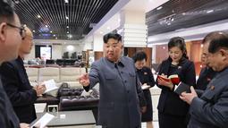 Pemimpin Korea Utara, Kim Jong-un berbincang dengan stafnya ketika berada di toko furniture saat mengunjungi Taesong Department Store setelah dibuka untuk umum di Korea Utara (8/4). (KCNA VIA AFP Photo)