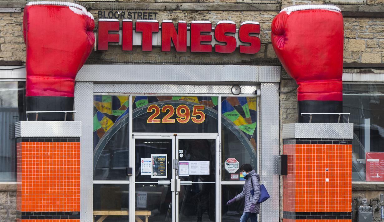 Seorang wanita yang mengenakan masker berjalan melewati pusat kebugaran yang tutup di Toronto, Kanada, 23 November 2020. Kanada melaporkan 5.119 kasus baru COVID-19 dan tambahan 49 kematian pada 23 November 2020 malam waktu setempat. (Xinhua/Zou Zheng)